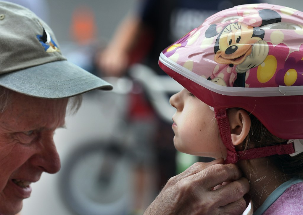 Robert McChesney secures Sophie Moore's bicycle helmet Sunday during the rodeo held at the Richmond Police Department for young riders in the community.