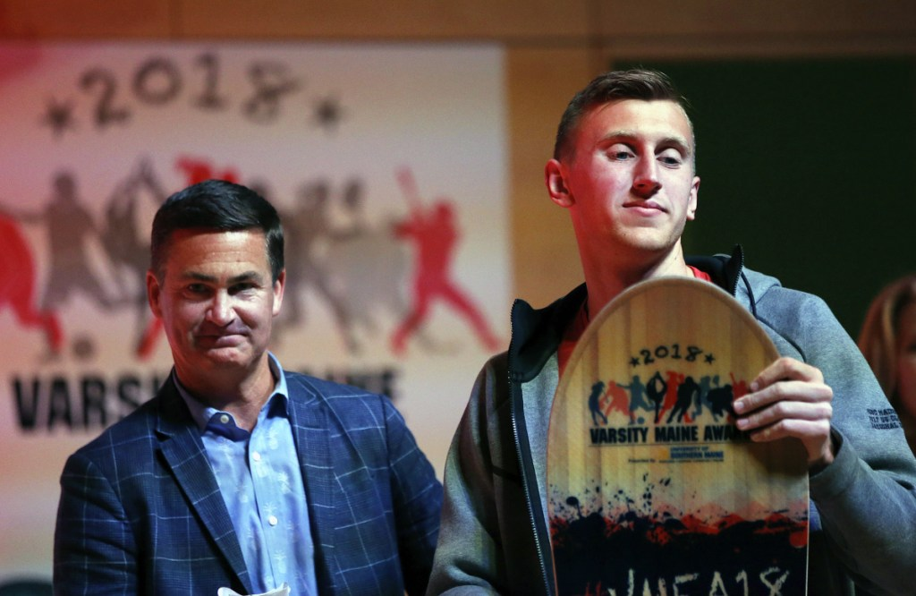 Cole Smith of Messalonskee High School, right, shares the stage with presenter Brian Corcoran, CEO of Shamrock Sports, after Smith won an Academic Ace award on Tuesday during the 2018 Varsity Maine Awards at Hannaford Hall on University of Southern Maine's Portland campus.
