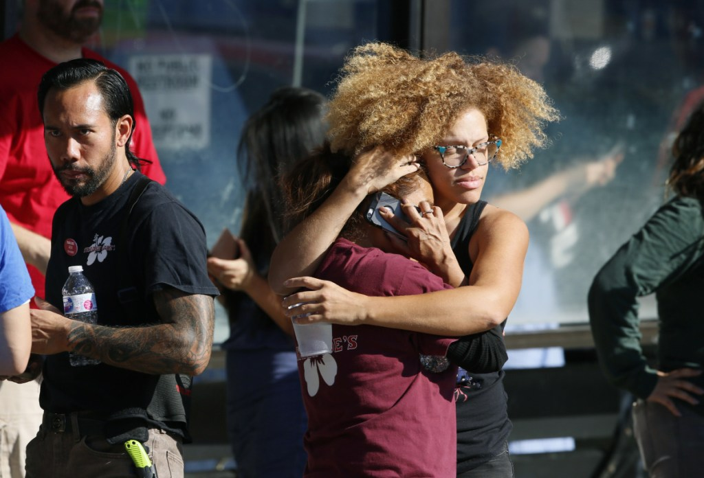 Unidentified Trader Joe's employees hug after Saturday's standoff, which ended when the gunman handcuffed himself and surrendered. Gene Evin Atkins faces a murder charge.