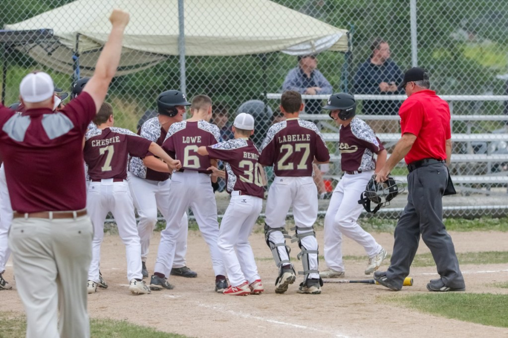 The Saco Little League team celebrates at home plate after Henry Lausier hit a three-run homer to finish off an 11-0 win over Lewiston in the state final Wednesday in Machias.