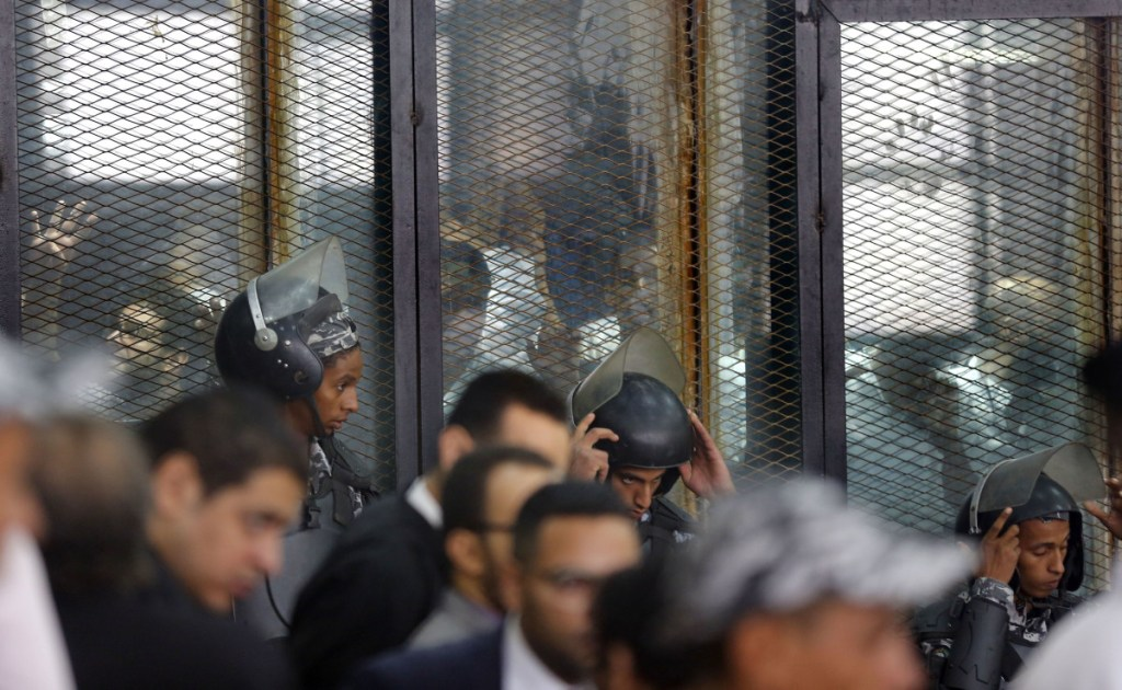 Police guard 739 defendants at a soundproof glass cage inside a makeshift courtroom in Tora prison in Cairo on Saturday. Egypt's state-run media says a court has sentenced 75 people to death, including top figures of the outlawed Muslim Brotherhood group, for their involvement in a 2013 sit-in.