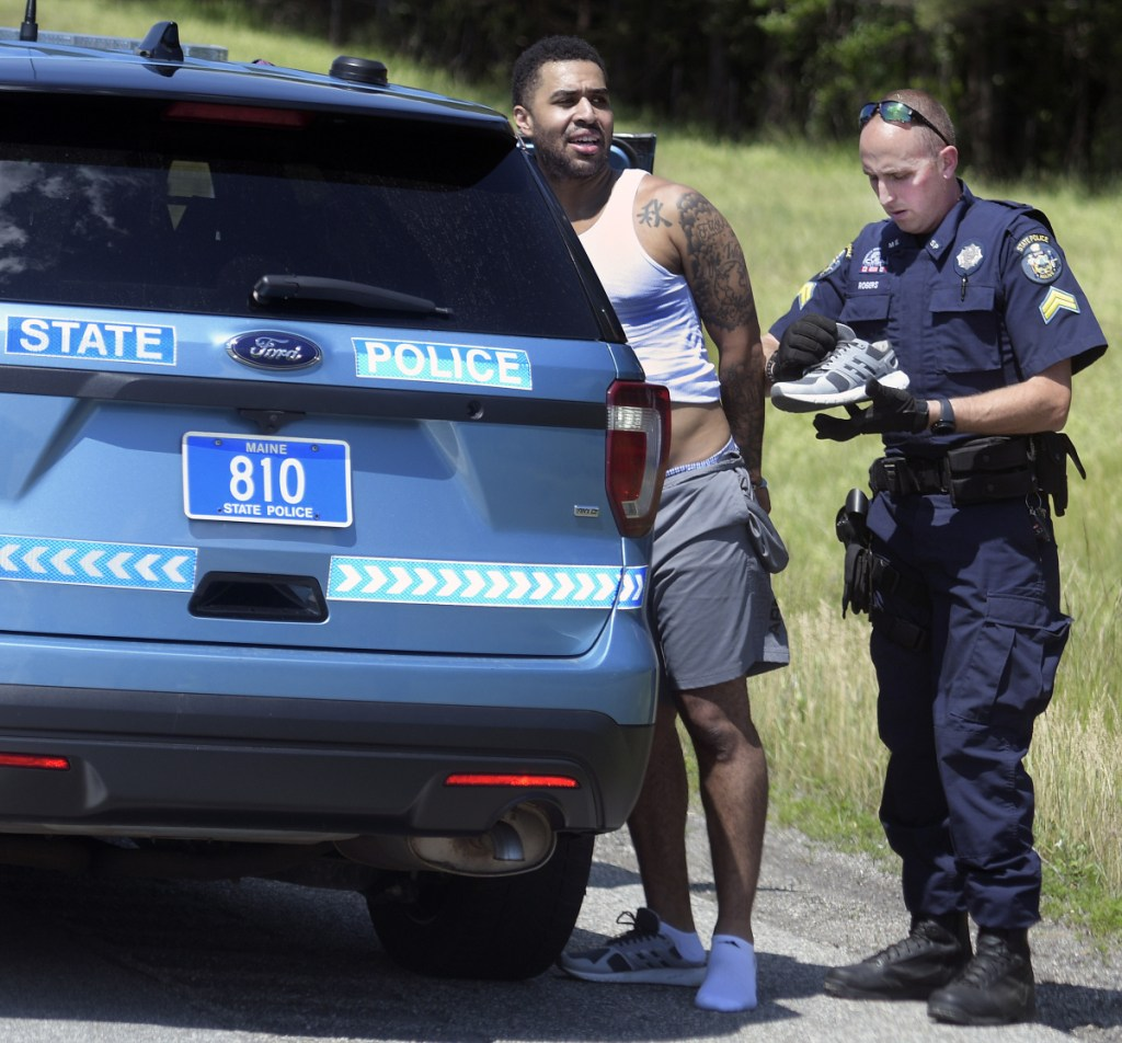 State Police Cpl. Christopher Rogers searches the clothes of a man he arrested Friday on the Maine Turnpike in Hallowell following a pursuit.