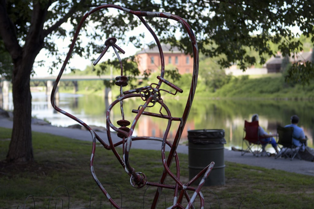 People watch sturgeon rise next to a sculpture next by the Kennebec River in Augusta on Wednesday.