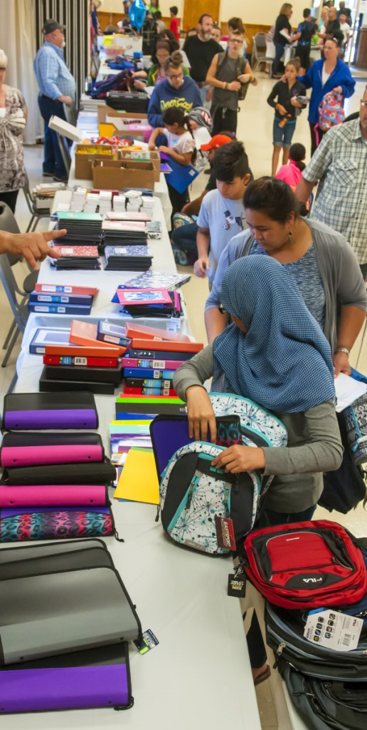 People pick up backpacks and school supplies Aug. 26, 2017, during a giveaway at the Augusta Elks Lodge.
