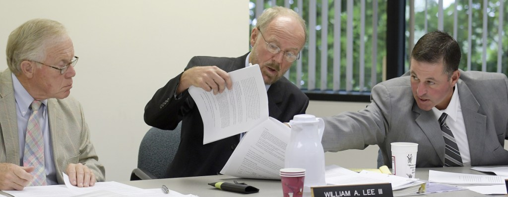 Maine Ethics Commissioners Richard Nass, left, Chairman William Lee III and Bradford A. Pattershall examine a document Wednesday while hearing a Clean Elections complaint from House District 110 Republican candidate Mark André, of Waterville, at the State Ethics Commission in Augusta.