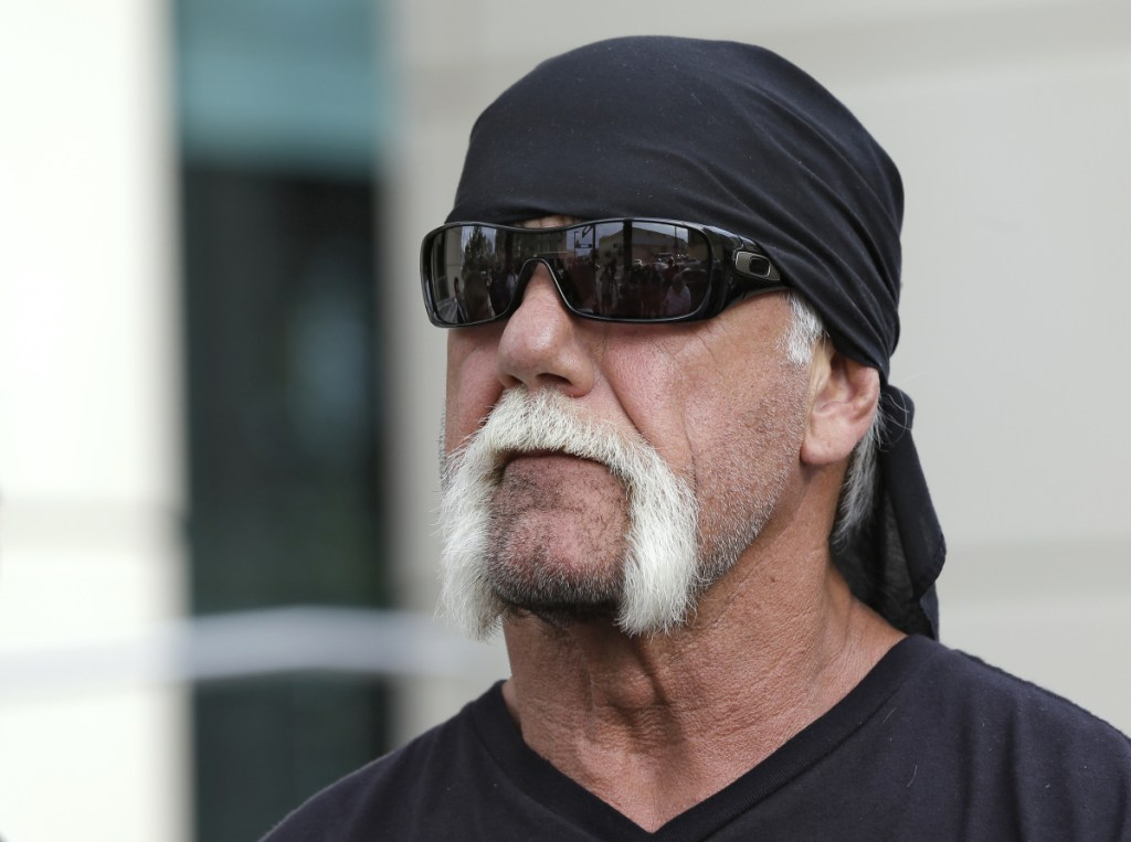 In this October 2012 photo, reality TV star and former pro wrestler Hulk Hogan, whose real name is Terry Bollea, looks on as his attorney speaks in Tampa, Florida. World Wrestling Entertainment Inc. has reinstated Hogan to its Hall of Fame, three years after he was found to have used racial slurs in a conversation caught on a sex tape.