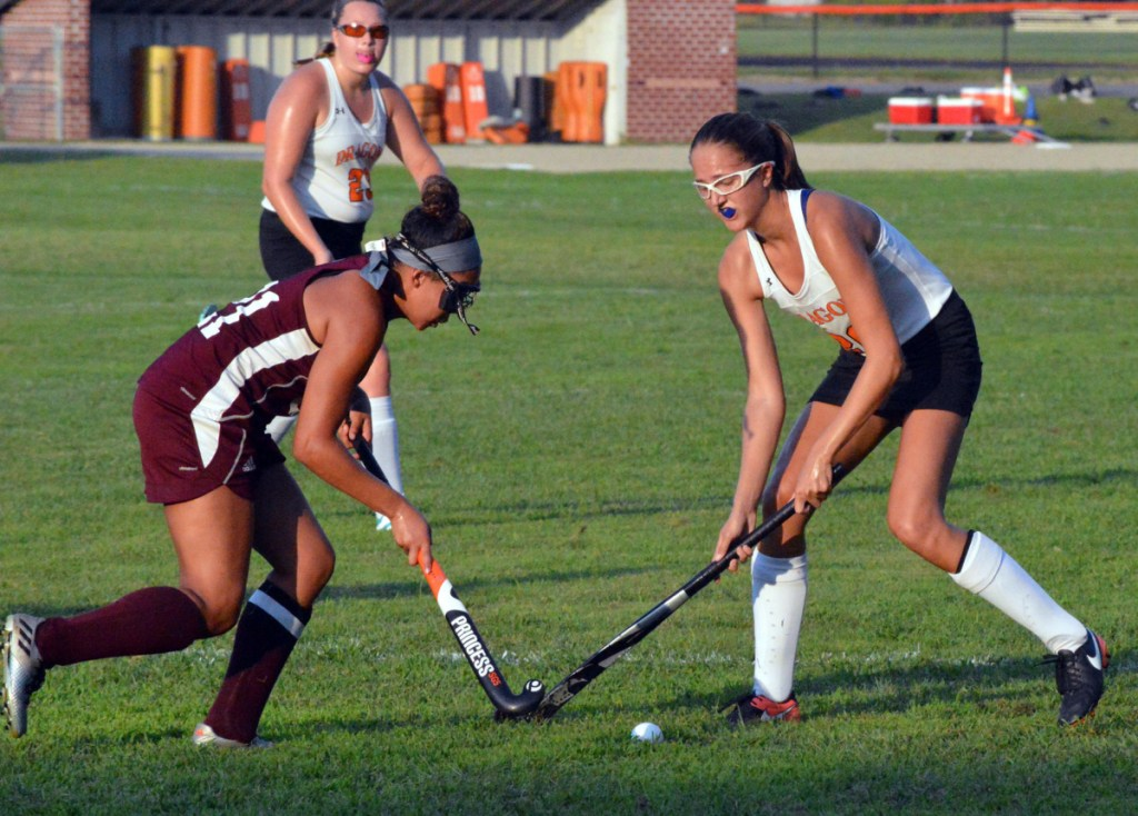 Kiara Fournier, left, of Edward Little battles for a loose ball with Brunswick's Erin Coughlin during their KVAC field hockey season opener Wednesday in Brunswick. Fournier was one of five goal scorers for the Red Eddies in a 5-0 victory.