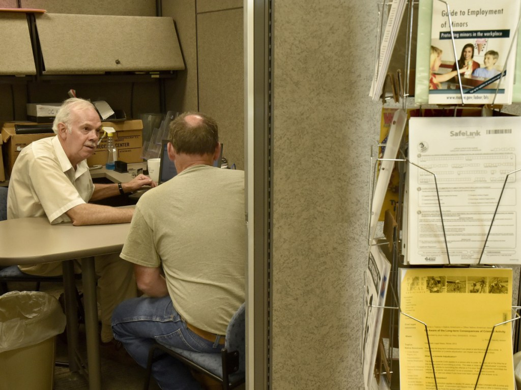 The Somerset Career Center has moved from Skowhegan into the Averill building on the Alfond Campus of Kennebec Valley Community College at Good Will-Hinckley in Fairfield, where it was open for business on Monday. Counselor Mike Shirley, left, assists Paul Tremblay in a room where clients may obtain employment resources and have access to computers.