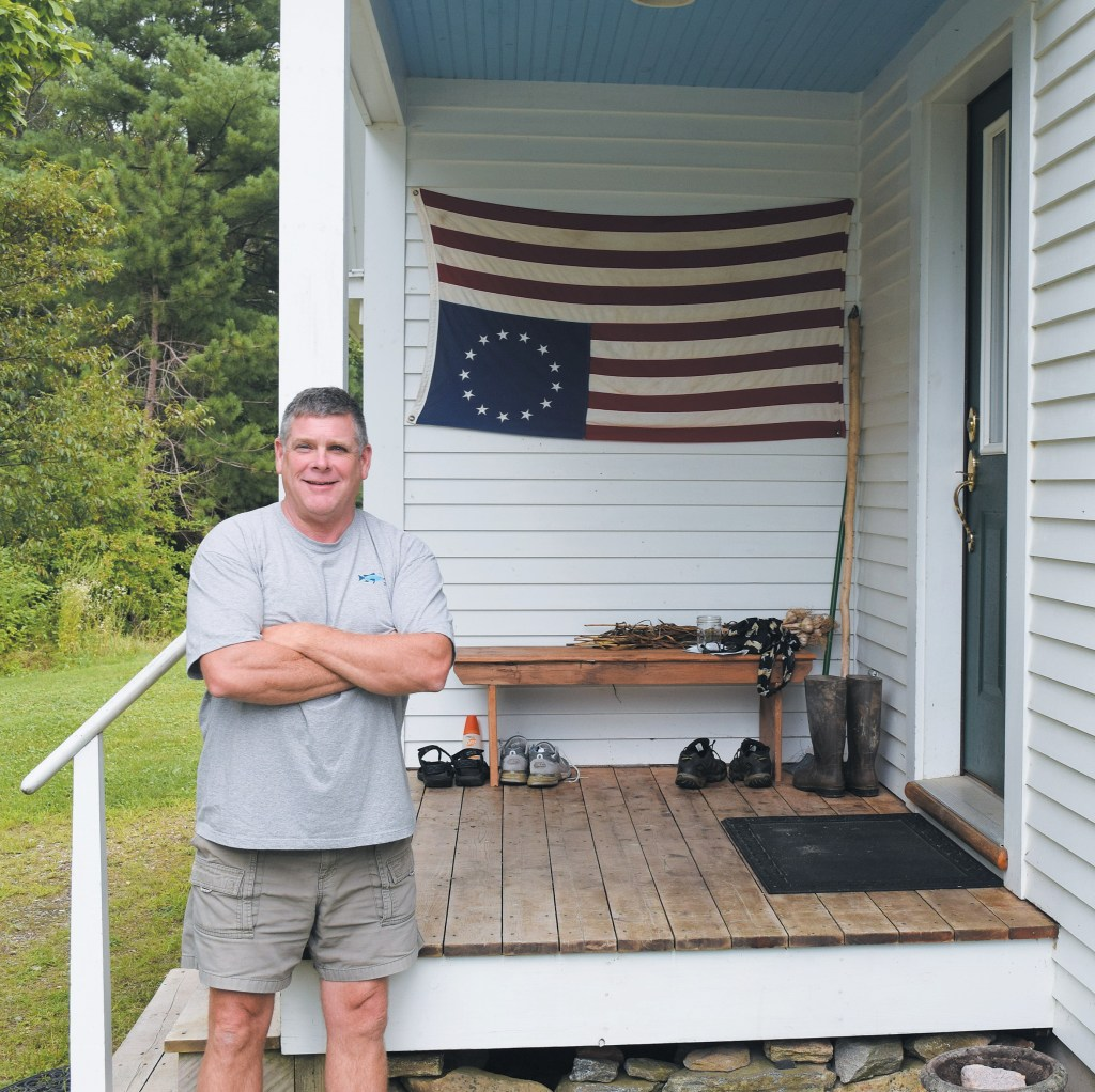 Bowdoinham resident Gregg McNally stands by the flag that has drawn attention from passers-by on Ridge Road. McNally said his intentions aren't to disrespect the flag, but to signal what he sees as a state of distress in the nation.