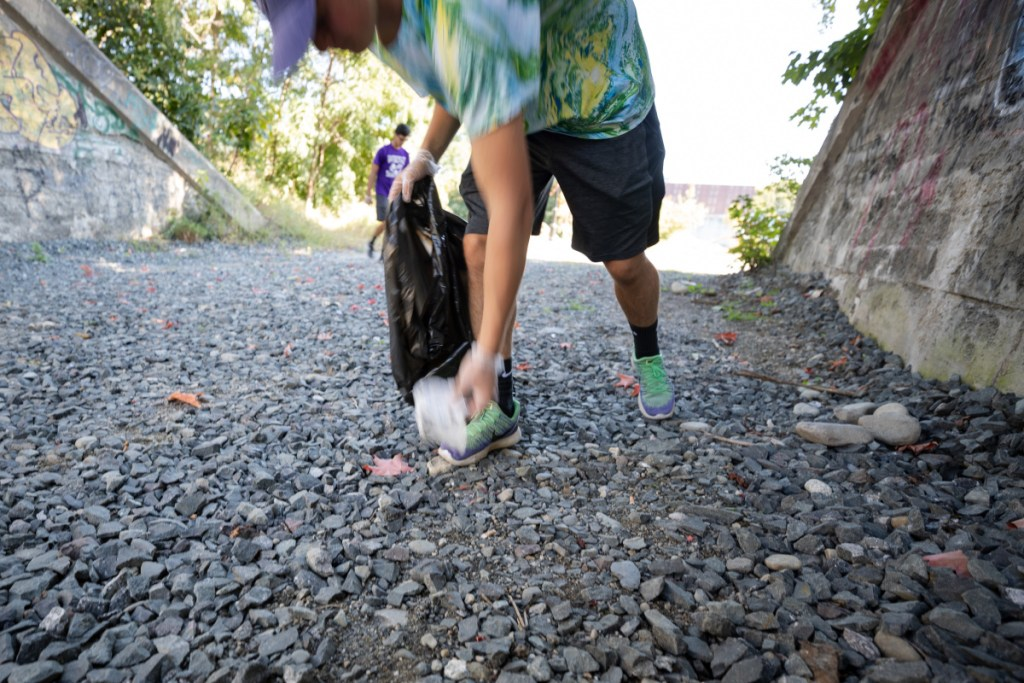 Conrad Ayers, 17, of Waterville High School's Green Team, picks up litter Saturday afternoon at the Head of Falls area in Waterville as part of a community litter cleanup event.