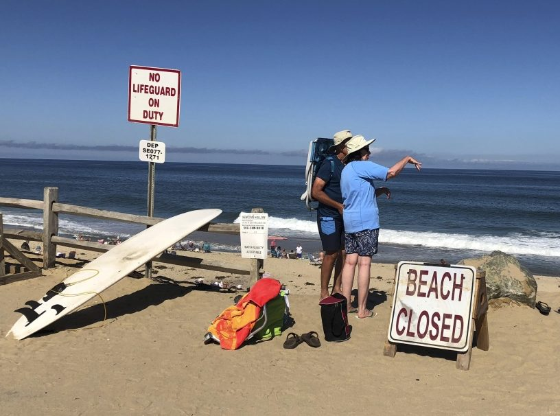 Two people look out from the shore after a shark attack at Newcomb Hollow Beach in Wellfleet, Mass, on Saturday.