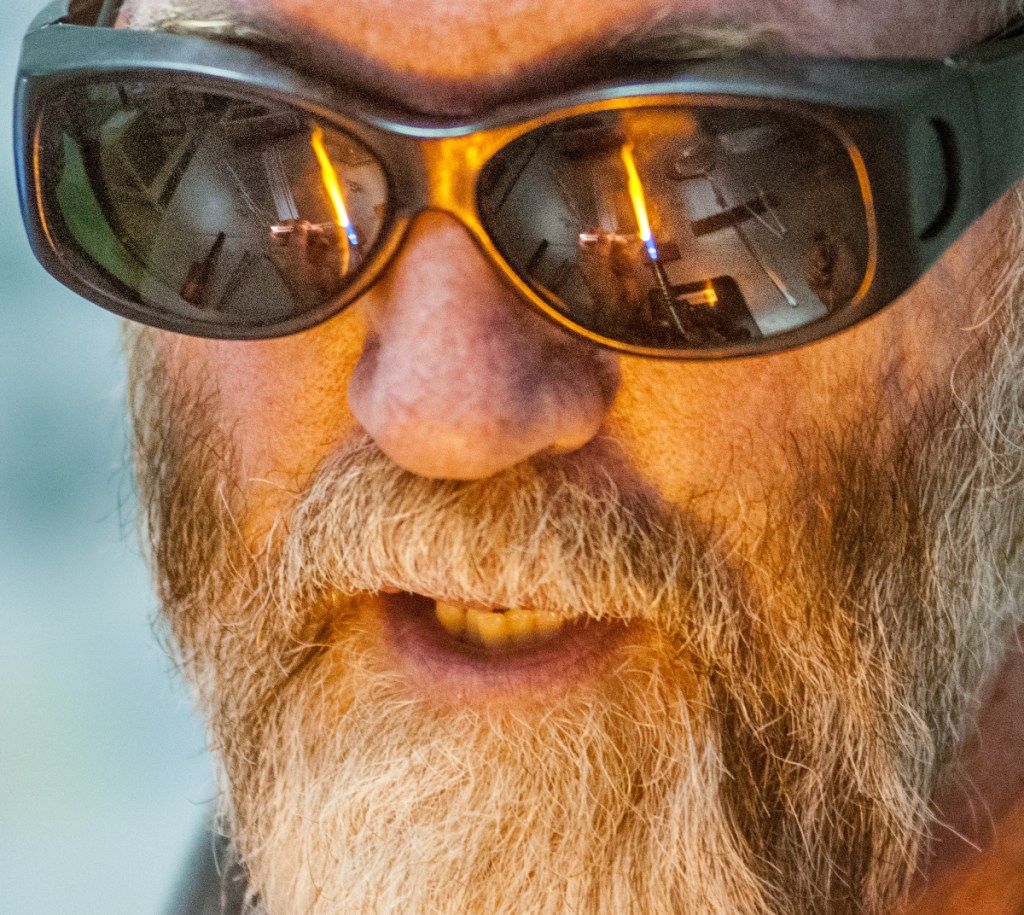 The torch used to heat glass is reflected in James Byrnes' glasses as he teaches a class on Saturday at Stained Glass Express in Manchester.