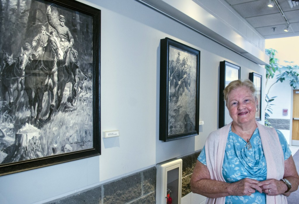"""Mary Mayo-Wescott poses for a portrait with the seven paintings given to Augusta by accomplished artist and city native William Herbert """"Buck"""" Dunton, depicting Civil War scenes on Aug. 31 at Augusta City Center. She was part of a city government committee that arranged to preserve and display them."""