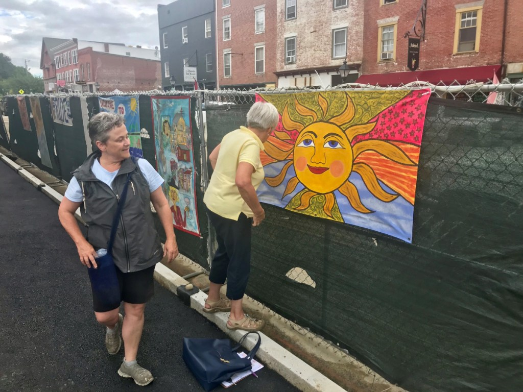 Deborah Fahy, left, Harlow Gallery executive director, and Nancy Bischoff, a member of the Down with the Crown Committee, hang a mural near the corner of Central and Water streets in Hallowell. Both women are involved in the Murals of the Fence project that hung artwork along construction fencing along Water Street.