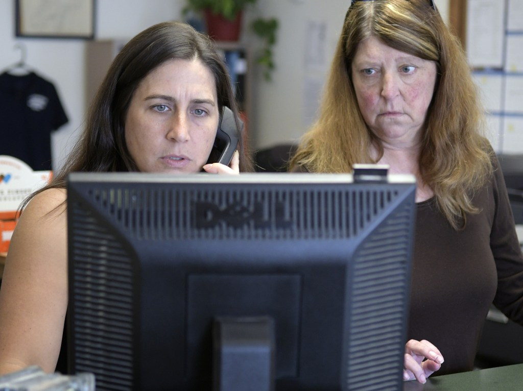 Deputy Clerk Lezley Sturtevant and Town Manager Trudy Lamoreau help a resident of Litchfield at the town office Thursday. The town lost about a month's worth of backup data when its computers crashed in July. Officials say they have now reproduced all the digital data from paper backups.