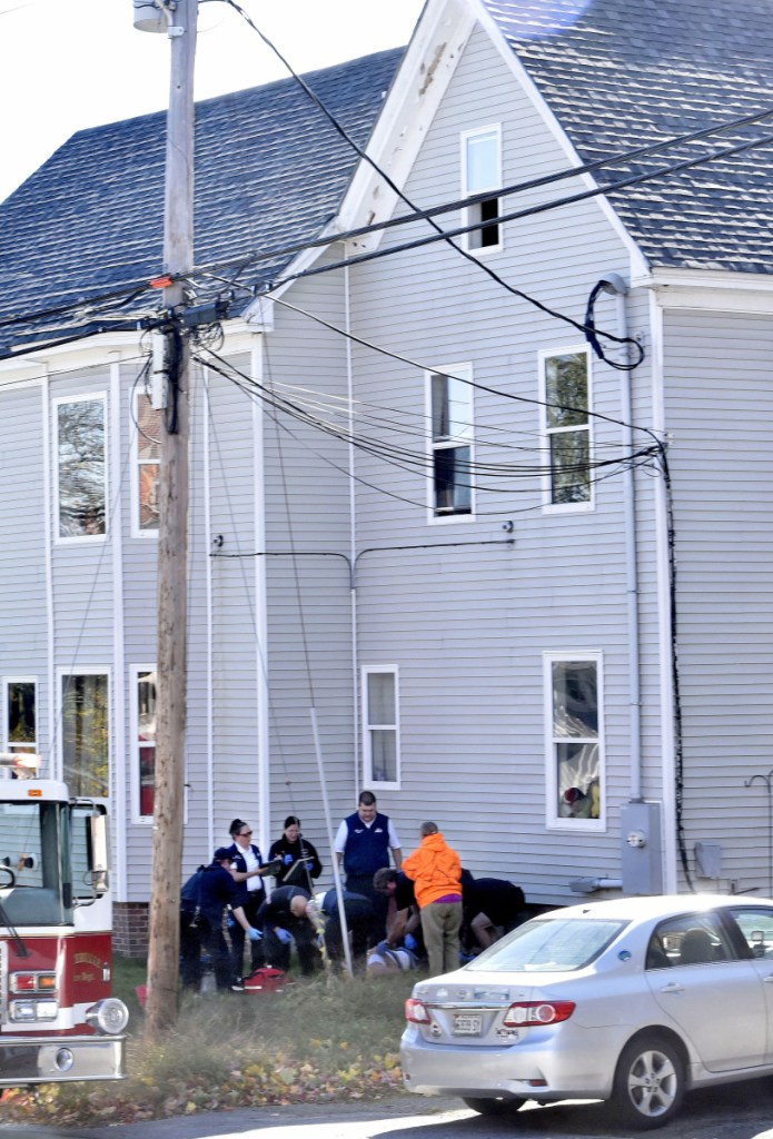Rescue and ambulance personnel administer aid to a man who reportedly fell Tuesday from the open third-floor window, above, at the Home Place Inn, an apartment complex on College Avenue in Waterville.