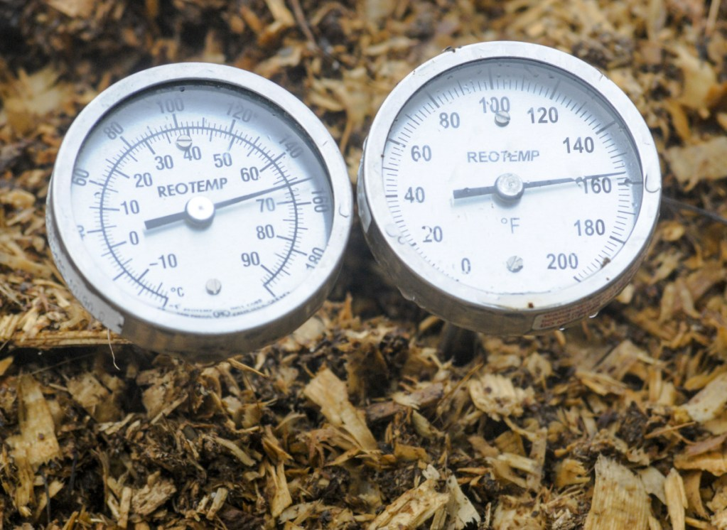 Thermometers, with different length probes, measure temperature on the edge and in the middle of compost piles Wednesday at Highmoor Farm in Monmouth.
