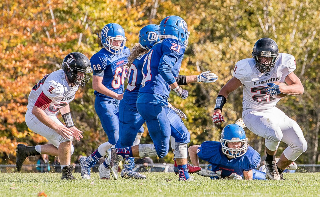 Lisbon's Isaiah Thompson, right, runs the balls down the field into Oak Hill's Hill's defense during Saturday afternoon's game in Wales.