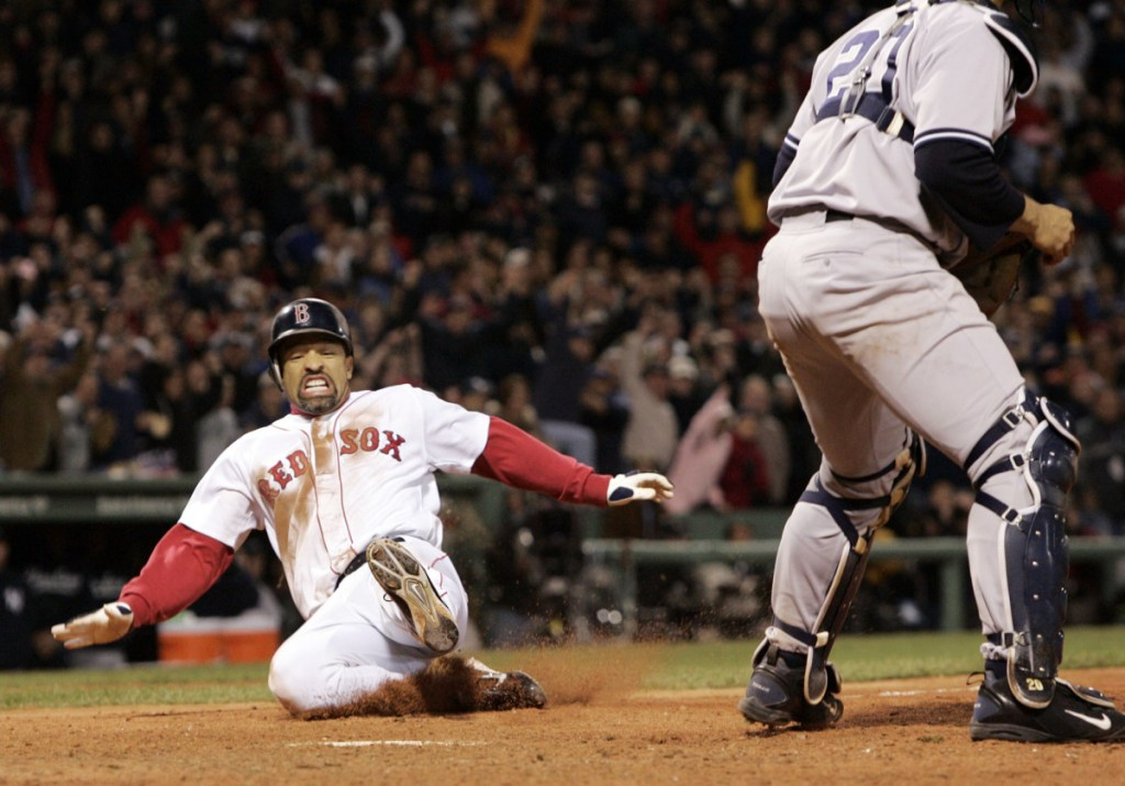 Boston's Dave Roberts, left, slides home to score the tying run past New York Yankees' Mariano Rivera in the ninth inning of Game 4 of the American League Championship Series in October 2004 in Boston. Roberts entered the game as a pinch-runner and came around to score as the Red Sox rallied to defeat the Yankees, come back from a 3-0 deficit in the series and go on to win their first World Series in 86 years. Roberts returns to Fenway Park on Tuesday as the Dodgers manager as Los Angeles faces Boston in the World Series.