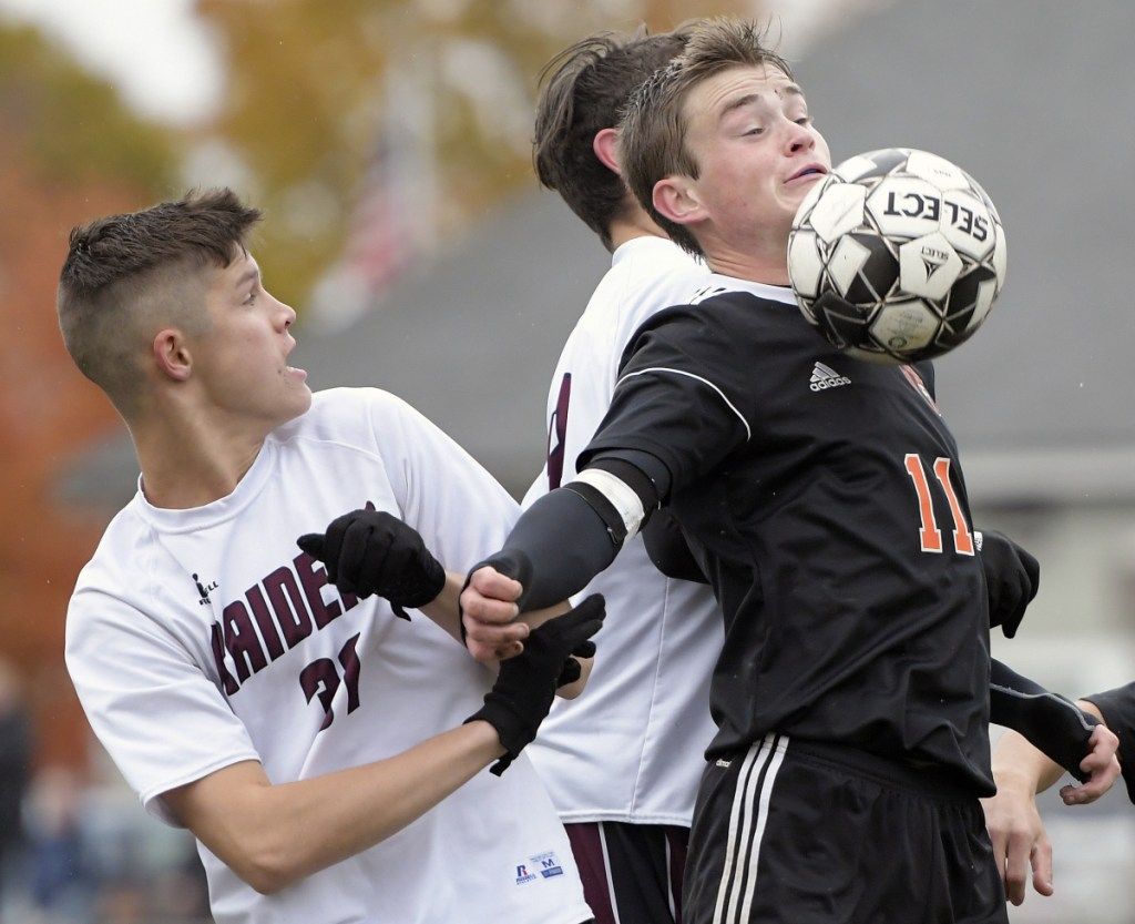 Gardiner's Casey Bourque, right, moves the ball away from Washington's defense during a Class B North quarterfinal game Tuesday in Gardiner.