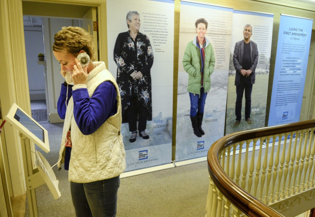 Toni Richardson listens to an interview of herself that's part of a display Tuesday at the First Amendment Museum in Augusta. Richardson, seen on the middle banner in the background, was interviewed about a controversy about religious speech in the workplace while working as an education technician in the Augusta school system.