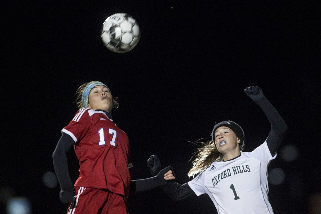 Staff photo by Michael G. Seamans   Messalonskee's Edin Sisson, left, battles for a header with Oxford Hills' Bella Divivo during a Class A North quarrerfinal game Tuesday night at Thomas College.