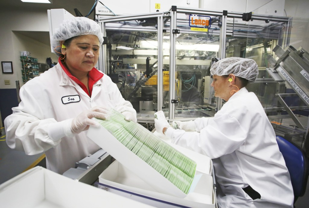 production specialist Sea Neak, left, works with trainee Patricia Phillips as they batch product in boxes for quality-control testing last week. Staff photo by Jill Brady