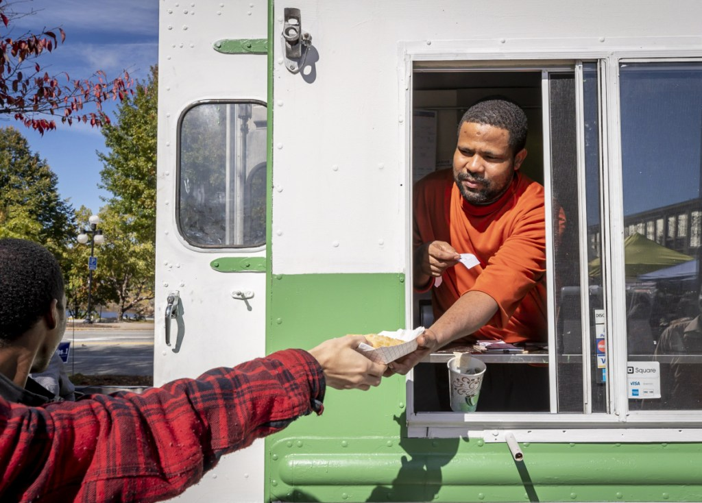 Isaak Gawo hands an order to a customer on Sunday. The Isuken Co-op truck has been making weekly trips to the Lewiston market. Most days though, it is parked on Sabattus Street in Lewiston, next to a farmstand operated seasonally by New Roots Cooperative Farm.