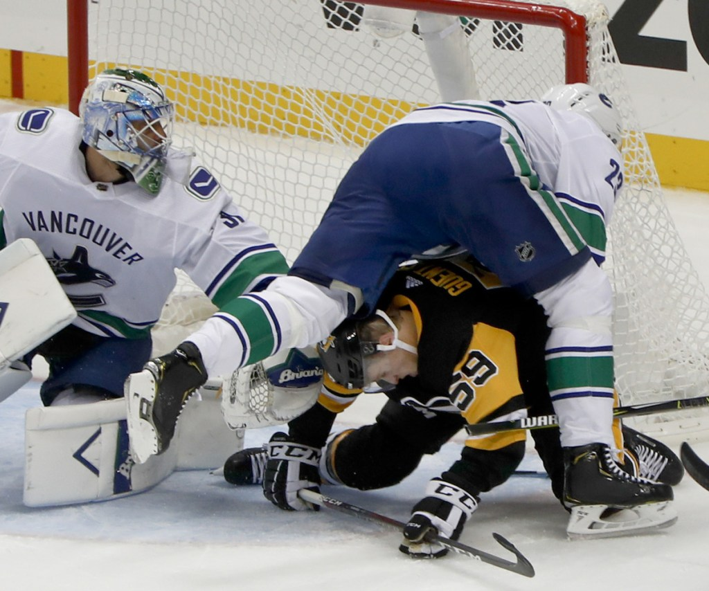 Canucks defenseman Alexander Edler, top right, tumbles over the Penguins' Jake Guentzel beside goaltender Anders Nilsson during the first period of Vancouver's 3-2 overtime win on Tuesday.