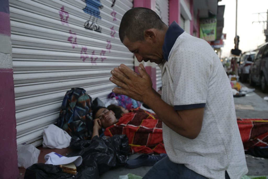 Marvin Sanabria, a Central American migrant traveling with a caravan to the United States, kneels in prayer after waking up in Huixtla, Mexico, on Tuesday. The caravan, estimated to include more than 7,000 people, had advanced but still faced more than 1,000 miles, and likely much farther, to the end of the journey.