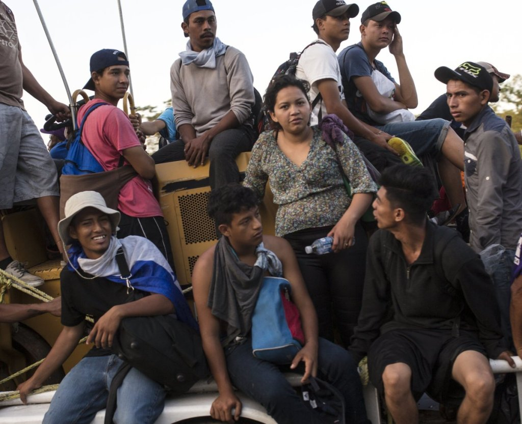 Central American migrants traveling with a caravan to the U.S. crowd onto a tractor as they make their through Mexico on Wednesday.