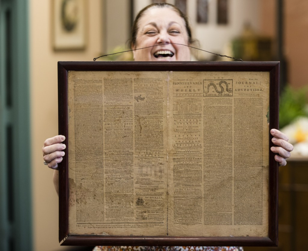 Heather Randall displays a Dec. 28, 1774 Pennsylvania Journal and the Weekly Advertiser at Goodwill Industries South Jersey in Bellmawr, N.J., Thursday. At left, two of the advertisements on the front page.