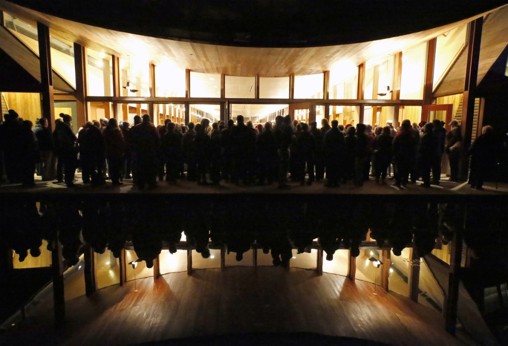 """People who couldn't get into the synagogue listen to the speakers from an outdoor patio area near a reflecting pool. Molly Curren Rowles of the Jewish Community Alliance called the response to the vigil """"remarkable."""""""