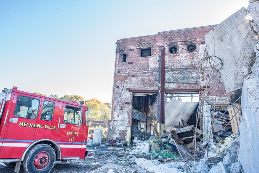 Firefighters remain at the former Marcal Paper mill in Mechanic Falls on Tuesday, as Sunday's fire continues to smolder.