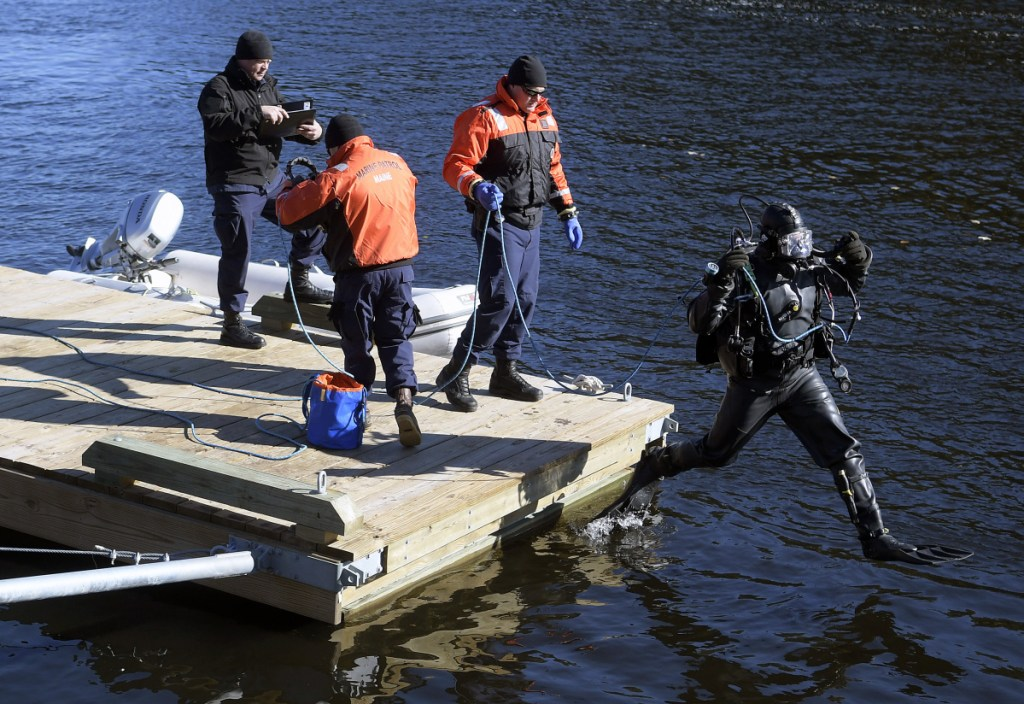 A diver from the Department of Public Safety's dive team leaps off a dock Friday on the Kennebec River in Richmond to search for Mark Johnston, who disappeared after leaving to move his boat from a mooring to the town dock.