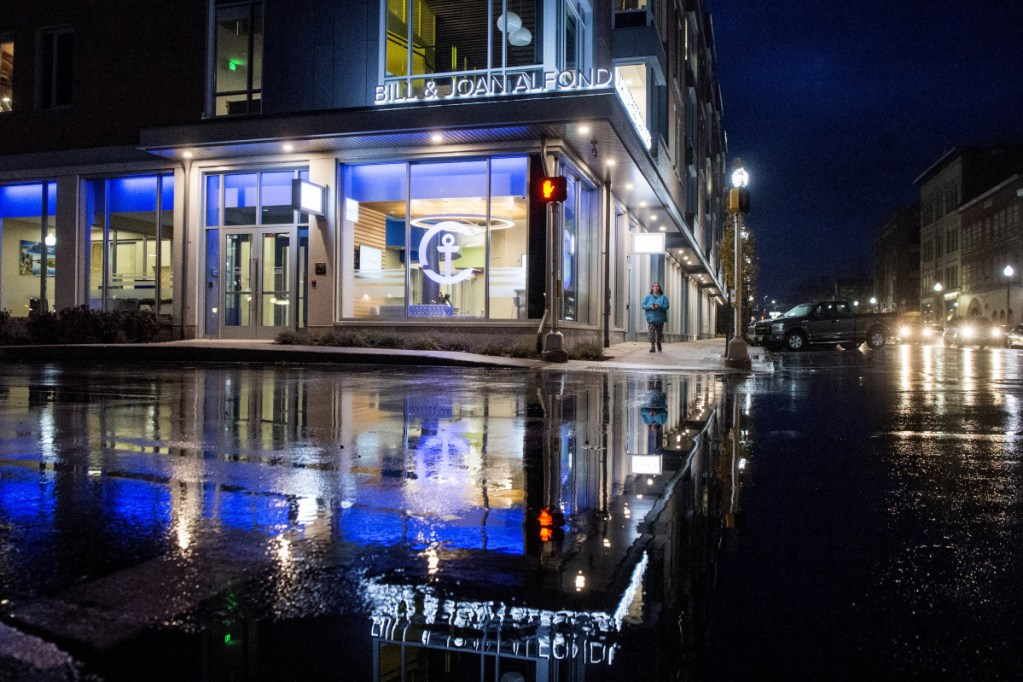 The newly constructed Bill & Joan Alfond Main Street Commons reflects in the water at the intersection of Temple Street and Main Street at night in Waterville on Nov. 1. Camden National Bank recently moved into the new downtown location.