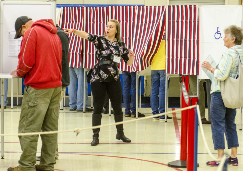 Deputy warden Kim Ward points voters to an open booth around 8:10 a.m. Tuesday at the Boys and Girls Clubs of Kennebec Valley in Gardiner. There were long lines just after the doors opened.