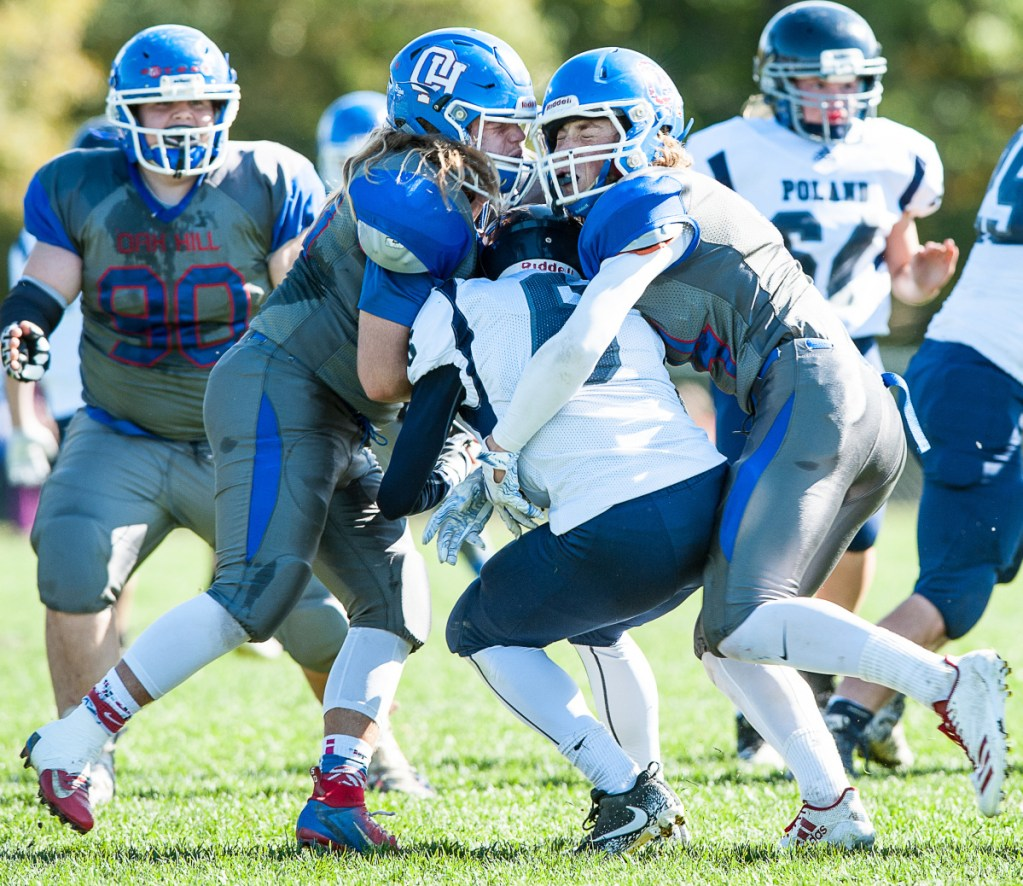 Oak Hill linebacker Ethan Richard, left, and teammate Samuel Lindsay, right, knock facemasks as they hit Poland quarterback Isaiah Hill in the backfield for a loss during the first half of a game earlier this season in Wales.