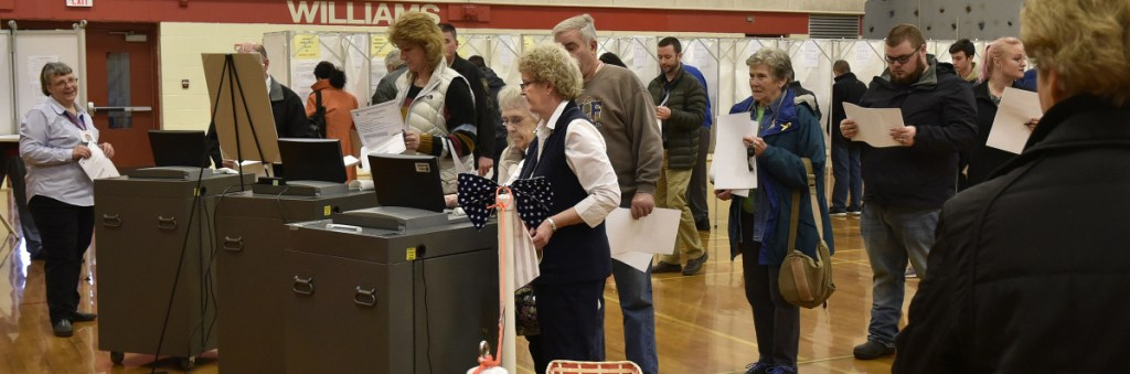 Oakland Town Clerk Jan Porter, center, assists a steady flow of voters Tuesday at the Williams School.