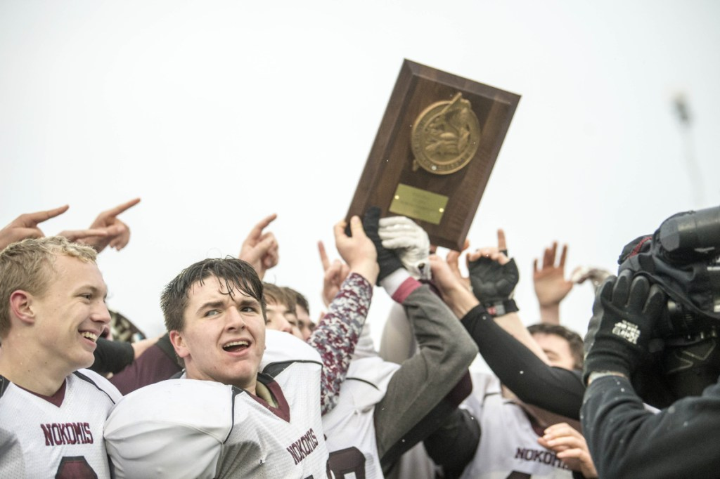 Staff photo by Michael G. Seamans   The Nokomis football team holds up the Class C North championship trophy after defeating Hermon on Saturday at Hampden Academy.