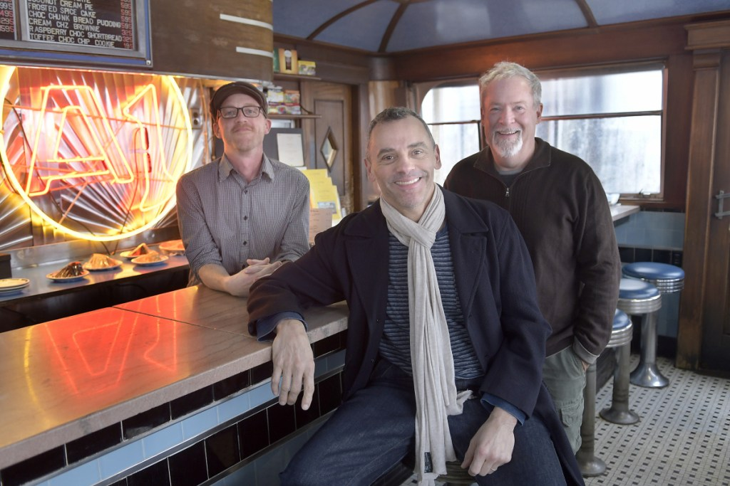 After three decades, Michael Giberson, right, and Neil Andersen, center, are handing the reins of the A1 Diner in Gardiner over to Aaron Harris. The men gathered at the renowned eatery on Monday.