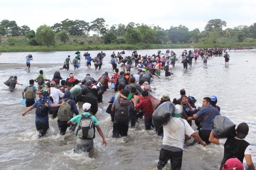 Salvadoran migrants wade across the Suchiate River, between Guatemala and Mexico, on Friday after Mexican officials told them they would have to show passports and visas and enter in groups for processing.