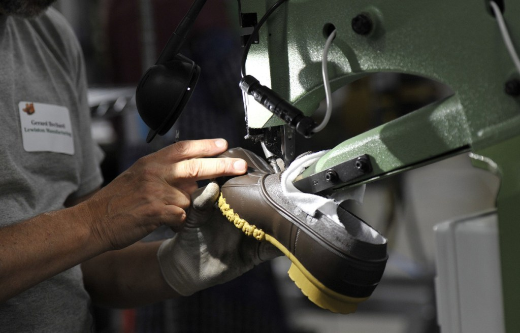 An L.L. Bean employee trims a boot being produced in the company's Lewiston plant. Sales of Bean boots continue to be strong, company CEO Steve Smith says.