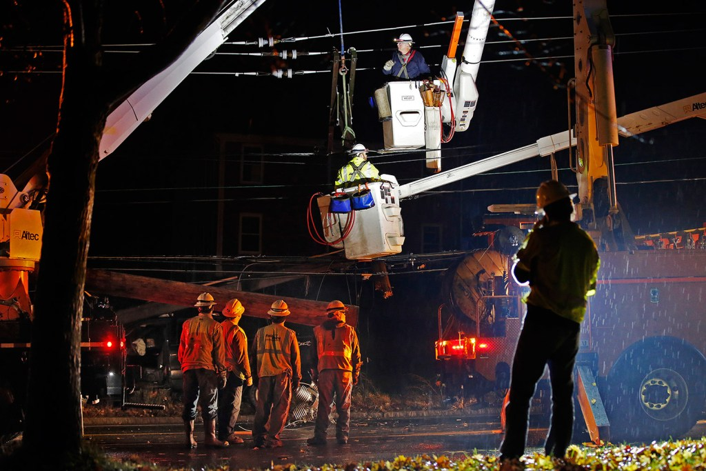Crews work Tuesday night to repair the utility pole that was broken when a car crashed into it. A section of outer Congress Street in Portland was closed during the repair, and power was out at the Portland International Jetport and nearby areas.