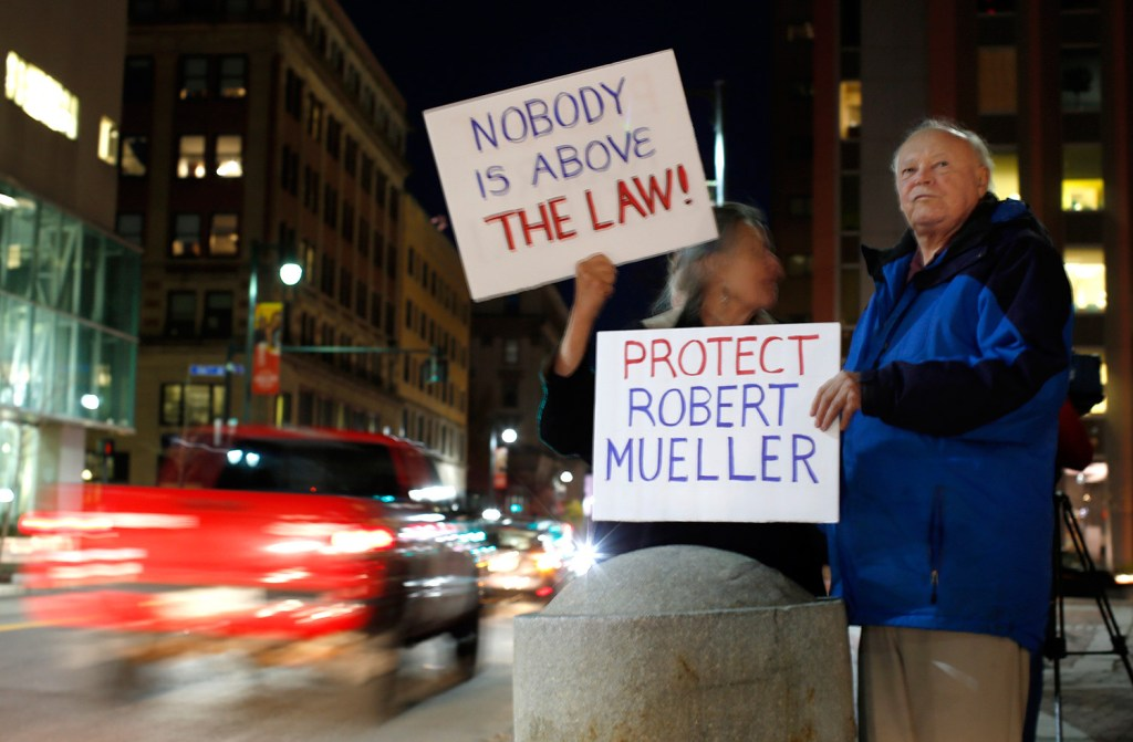 Marilyn Sarelas and Jim White of Portland display signs to drivers on Congress Street during Thursday's protest at Monument Square.