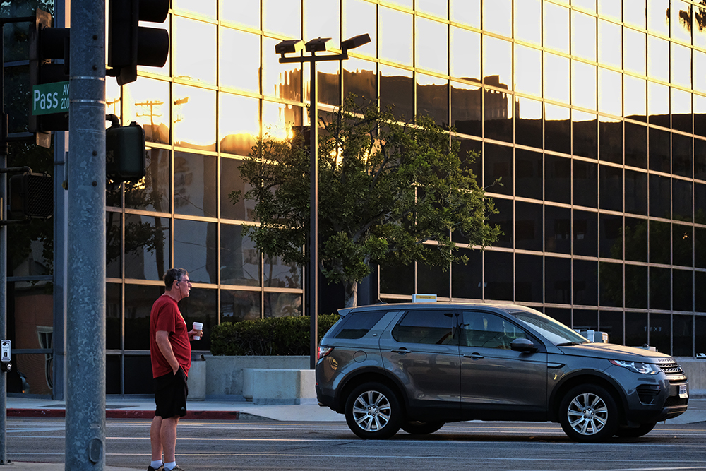 A man with his morning cup of coffee in hand crosses a street as the sun rises in the reflection of a building in Burbank, Calif. in September. This November, California voters will vote on Proposition 7 that would pave the way for year-round daylight saving time in the state.