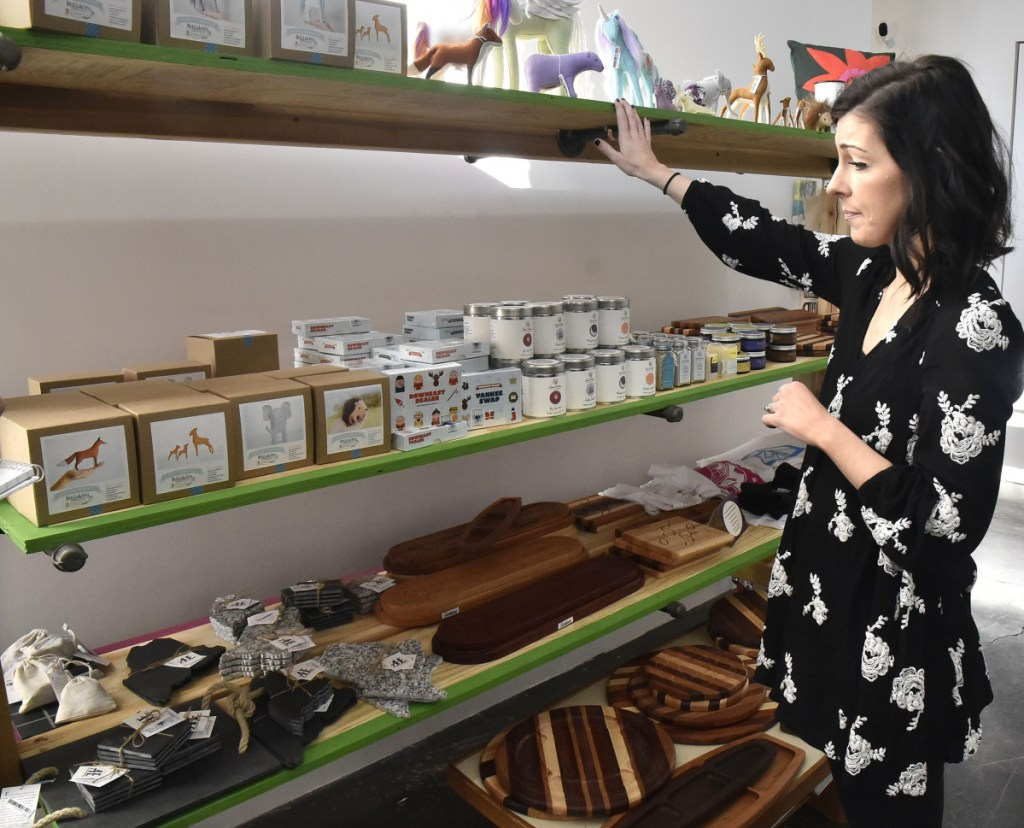 Marie Sugden looks over novelties including handmade wood products and children's toys at the holiday bazaar shop at Common Street Arts in the Hathaway Creative Center in Waterville on Thursday.