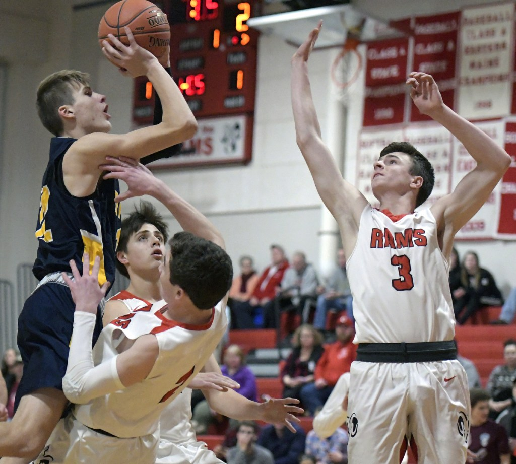 Cony's Dakota Dearborn defends Mt. Blue's Jacob Farhnam as he goes up for two during a Kennebec Valley Athletic Conference game Thursday in Augusta.