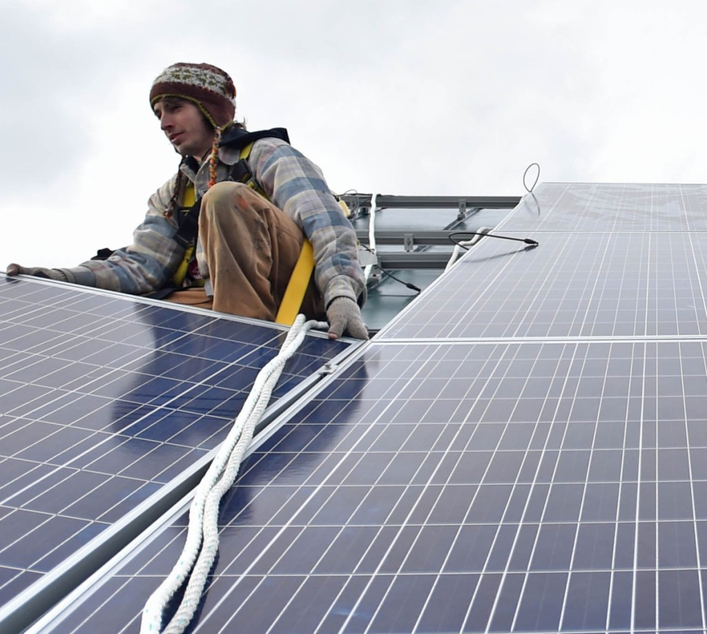 Ben Holt of InSource Renew- ables installs a solar panel on the Vassalboro Friends Meeting House in 2016.
