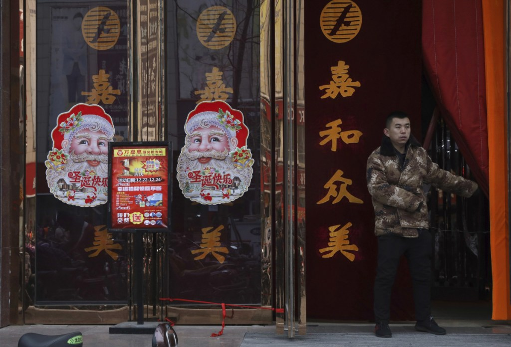 """A worker guards the entrance of a shop in Zhangjiakou in northern China's Hebei province on Saturday. The squeeze on Christmas shows how efforts to """"normalize"""" thinking bleed into the everyday lives of many Chinese."""